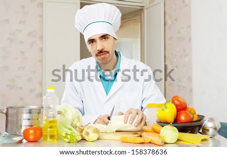Portrait of male cook with lettuce on cutting board at kitchen - stock photo