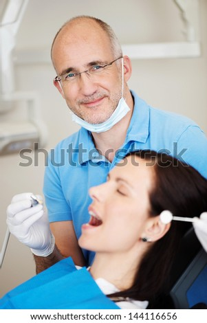 Portrait of male dentist examining female patient's mouth in clinic - stock photo