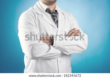 Portrait of male doctor physiotherapist standing in lab uniform with crossed arms over blue background. Healthcare and medicine concept.  - stock photo