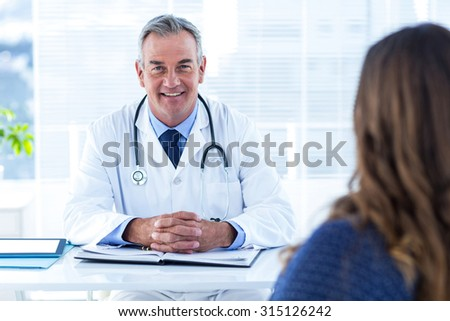 Portrait of male doctor sitting with woman at desk in hospital