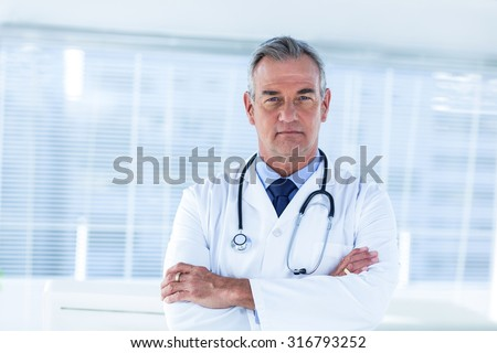 Portrait of male doctor standing arms crossed in hospital - stock photo