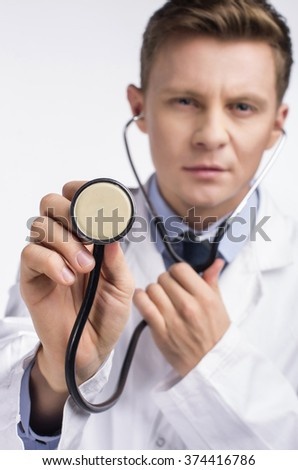Portrait of male doctor with stethoscope engaged in his work. - stock photo