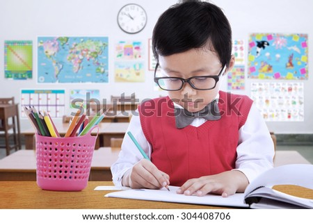 Portrait of male elementary school student wearing glasses in the class while drawing on the paper - stock photo