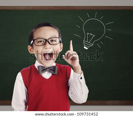 Portrait of male elementary school student with lightbulb picture on blackboard - stock photo