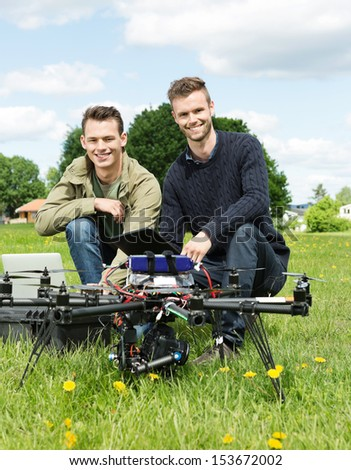 Portrait of male engineers with laptop and digital tablet by UAV at park - stock photo