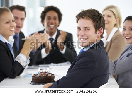 Portrait Of Male Executive Celebrating Birthday In OfficeWith Colleagues - stock photo