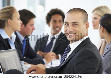 Portrait Of Male Executive With Office Meeting In Background
