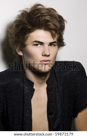 Portrait of male fashion model with stylish hairstyle and makeup - stock photo