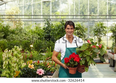 portrait of male florist looking at camera and holding plants - stock photo