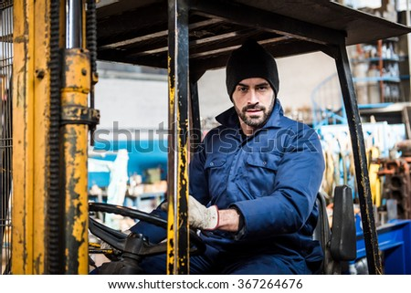 Portrait Of Male Fork Lift Truck Driver In Factory  - stock photo