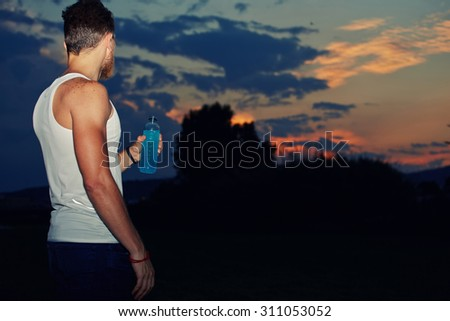 Portrait of male jogger holding bottle of energy drink in the hand while resting after active run outdoors,runner enjoying scenery evening sky with copy space area for your text message or advertising - stock photo
