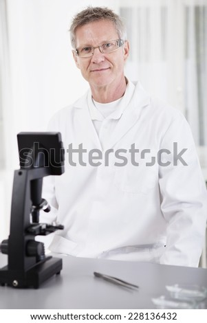 portrait of male medical or scientific researcher with microscope in a laboratory - stock photo