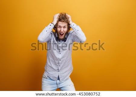 Portrait of male model tearing hair in hysteria on yellow background. Isolated. Big sale concept. - stock photo