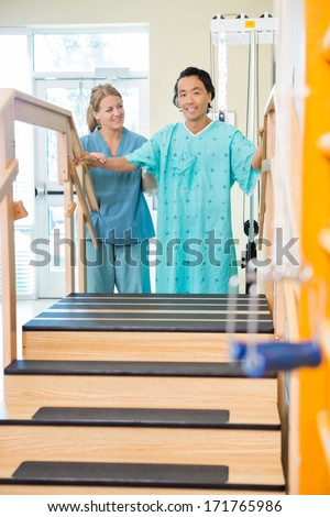 Portrait of male patient being assisted by physical therapist in moving upstairs - stock photo