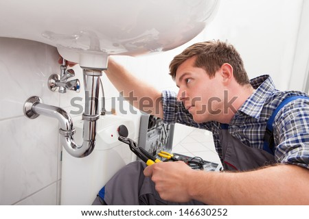 Portrait of male plumber fixing a sink in bathroom