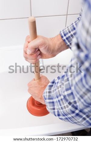 Portrait Of Male Plumber Using Plunger In Bathroom Sink - stock photo