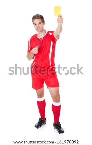 Portrait Of Male Soccer Referee Holding Yellow Card - stock photo