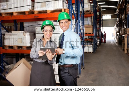 Portrait of male supervisor using digital tablet with colleague at warehouse - stock photo