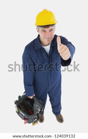 Portrait of male technician with tool bag gesturing thumbs up over white background - stock photo