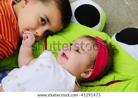 Portrait of male toddler and baby girl with happy expression - stock photo