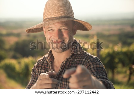 Portrait of male vintner with hat posing at vineyard