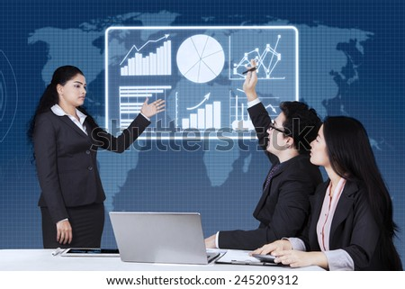 Portrait of male worker raising hand and enquiring on his leader in a business meeting at the office - stock photo