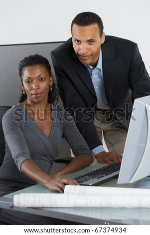 Portrait of man and woman at desk with computer - stock photo