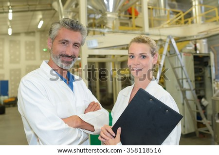 Portrait of man and woman in factory - stock photo