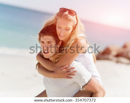 Portrait of man carrying girlfriend on his back on the beach