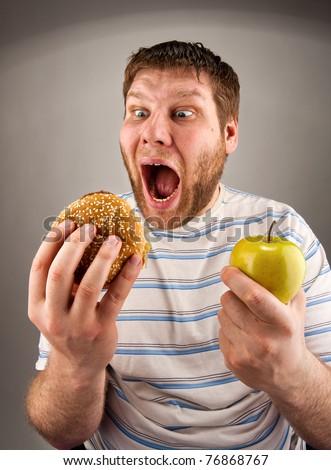 Portrait of man choosing between hamburger and green apple - stock photo