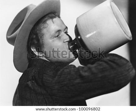 Portrait of man drinking from jug - stock photo