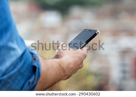 Portrait of man hand holding mobile phone in the city. - stock photo