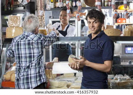 Portrait Of Man Holding Cheese And Mobilephone At Shop