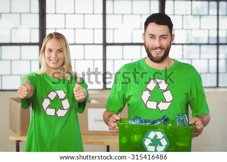 Portrait of man holding container with colleague showing thumbs up - stock photo