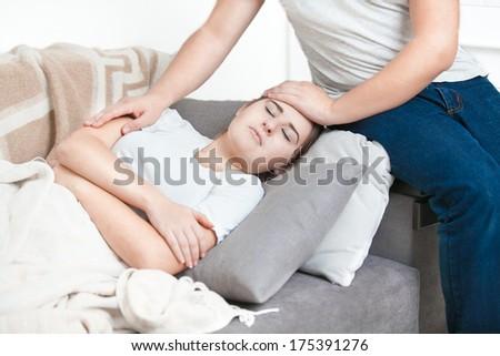 Portrait of man holding hand on sick women head - stock photo