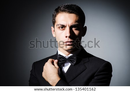 Portrait of man in dark studio - stock photo