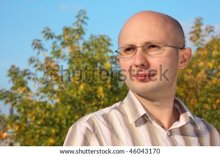 portrait of man in early fall park.he is looking away - stock photo