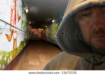 Portrait of man in hoody looking sinister - deliberately dark - stock photo