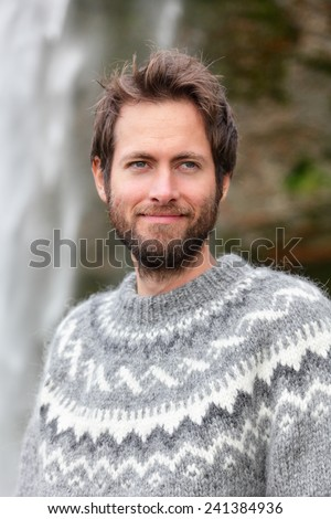 Portrait of man in Icelandic sweater outdoor smiling by waterfall on Iceland. Portrait of good looking bearded male model in nature. - stock photo