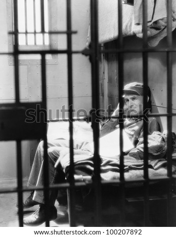 Portrait of man in jail - stock photo