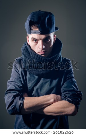 Portrait of man in scurf and cap with cupped hands on gray copy space background