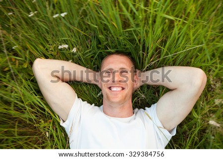 Portrait of   man lying on   green summer meadow.  - stock photo