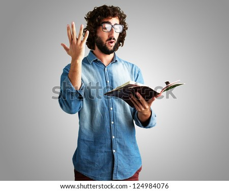 Portrait Of Man Reading Book against a grey background