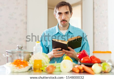 Portrait of man reading cookbook in domestic kitchen at home - stock photo