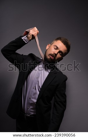 Portrait of man sad disappointed in elegant black suit hanging himself with tie and showing his tongue  on grey background waist up  - stock photo