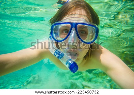 Portrait of man snorkeling in crystal clear lagoon water on tropical island - stock photo