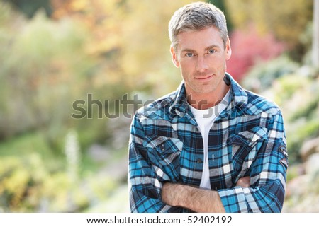 Portrait Of Man Standing Outside In Autumn Landscape - stock photo