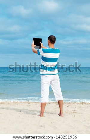 Portrait of man using tablet computer in  coastline, - stock photo