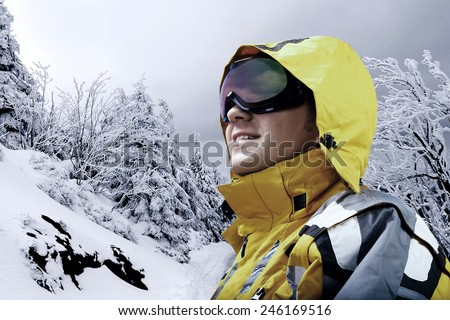 Portrait of man wearing a helmet and glasses on the background of snow winter and mounts. - stock photo