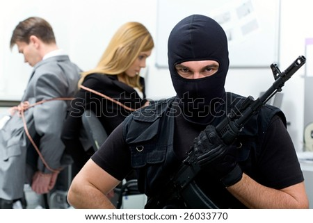 Portrait of man wearing black balaclava with gun looking at camera on background of scared business people - stock photo